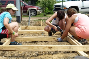 Students work to construct concrete forms at the Baptist Town pocket park.