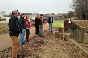Local residents visit the Tanglefoot Trail bridge in Houston to begin visioning for wayfinding improvements.